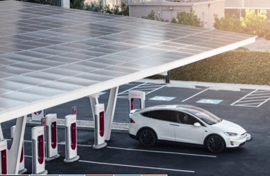 auto elektromobil Tesla Model X se nabíjí u nabíjecí stanice Tesla Supercharger doplněné o solární střešní elektrárnu